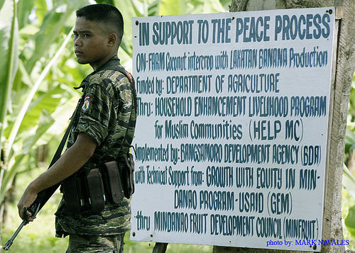 Young MILF fighter in front of peace poster, Mindanao, Philippines