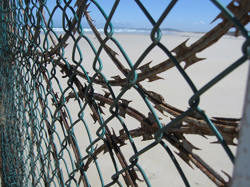 a rusty fence on the beach