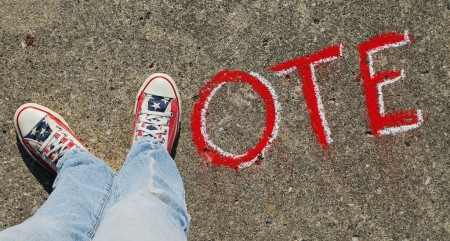 vote sign on sidewalk